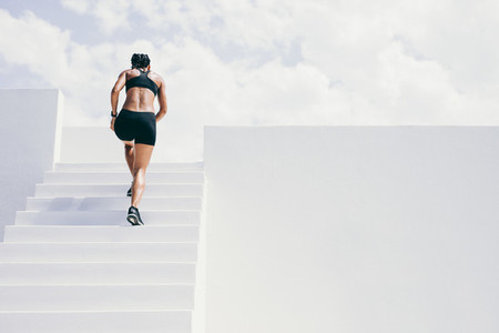 Fitness woman running up the stairs of a building