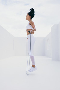 Woman doing fitness training using a skipping rope