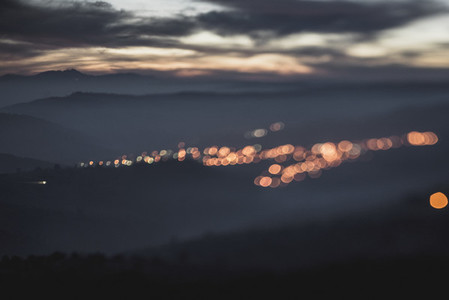 Blurry bokeh lights in dusk mountains