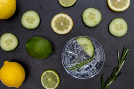 Gin tonic cocktail drink glass with ice cucumber lime lemon dark