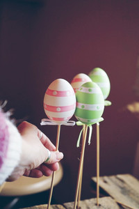 A beautiful close up of 3 easter eggs on sticks over tables with