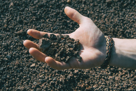 Close up of a human hand holding some volcanic rocks