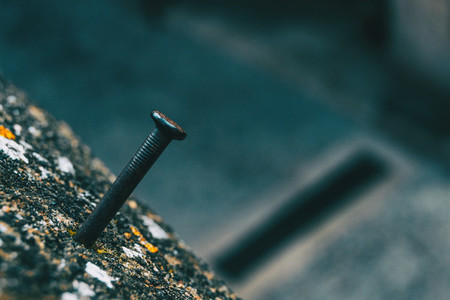 Detail of a nail stuck to a moldy stone