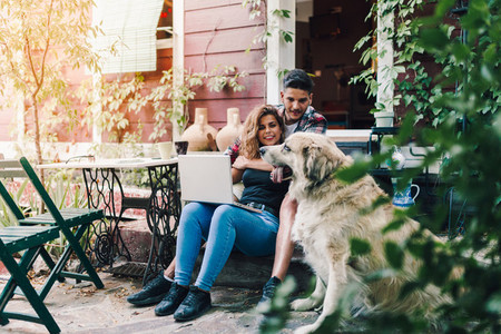 Young couple and their dog sitting smiling in the garden chairs near their wooden house with a laptop