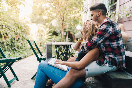 Young couple sitting embraced in the steps of their wooden house with a laptop