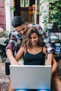 Smiling young couple sitting embraced in the steps of their wooden house with a laptop