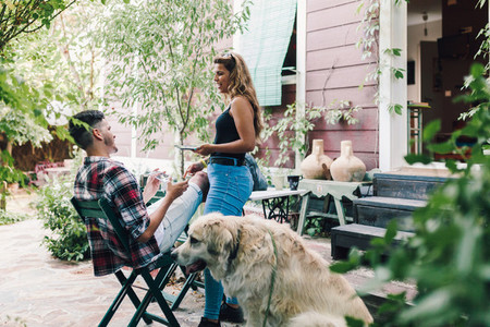 Young couple and their dog sitting smiling in the garden chairs near their wooden house
