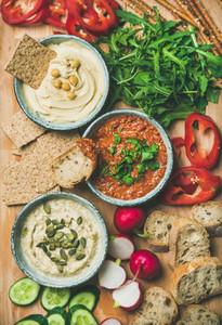 Vegan snack board  Flat lay of Vegetarian dips hummus  babaganush  muhammara