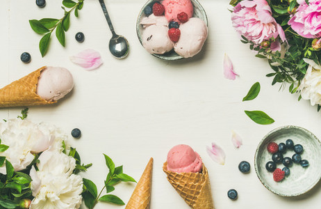 Flatlay of ice cream scoops and peonies over white background