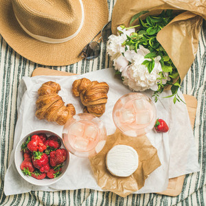 Flat lay of rose wine  strawberries  croissants  brie cheese  square crop