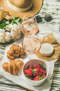 Flat lay of rose wine  strawberries  croissants  brie cheese on board