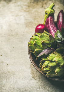 Flat lay of green and purple vegetables on plate copy space