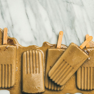 Flatlay of melting coffee latte popsicles  copy space  square crop
