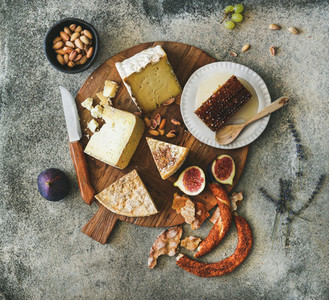 Flat lay of cheese assortment figs honey bread and nuts