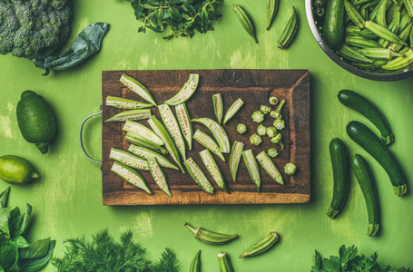 Flay lay of green vegetables and greens on wooden board