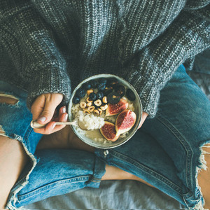 Woman in shabby jeans and sweater eating breakfast  square crop