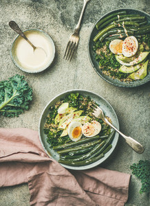 Quinoa kale green beans avocado egg bowls over concrete background