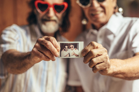 Retired friends sharing their old photograph