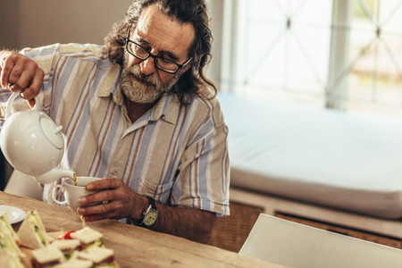Elderly man with beard pouring tea in cup