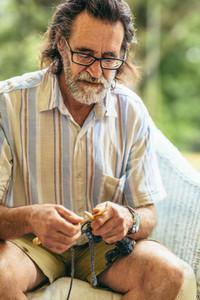 Senior man knitting while sitting on chair