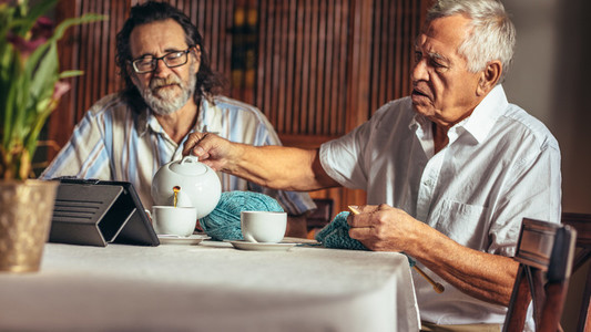 Senior friends relaxing at home having tea while knitting