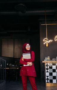 Hijab girl with laptop standing at cafe