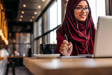 Female in hijab at cafe having video conference on her laptop
