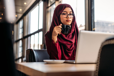Muslim woman working on laptop at a cafe