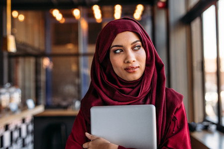 Businesswoman in hijab with laptop at cafe looking away
