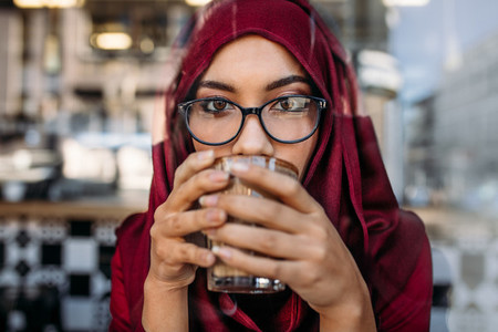 Muslim woman having coffee at cafe