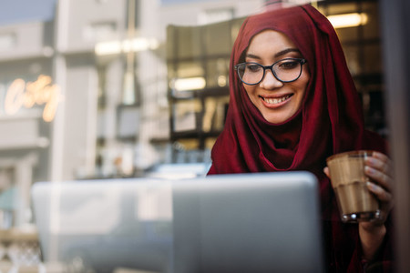 Smiling muslim woman using laptop at cafe
