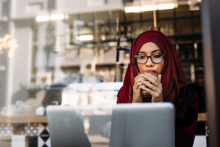 Woman in hijab using laptop and having coffee at cafe