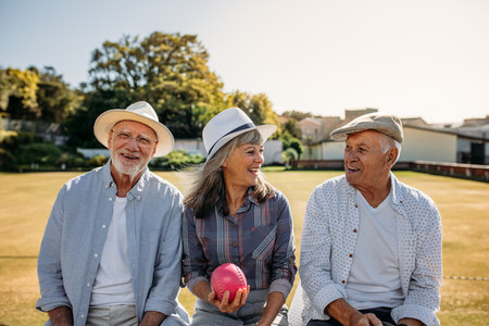Senior friends sitting outdoors and laughing