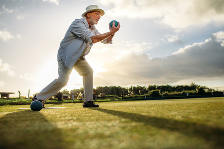 Side view of an elderly man playing boules