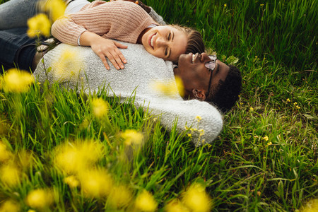Beautiful young couple lying in green grass