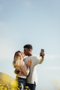 Interracial couple kissing and taking selfie