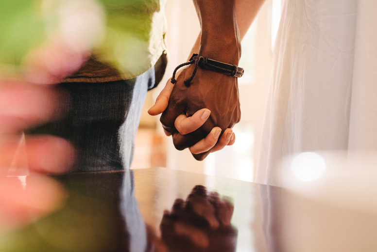Young man and woman holding hands