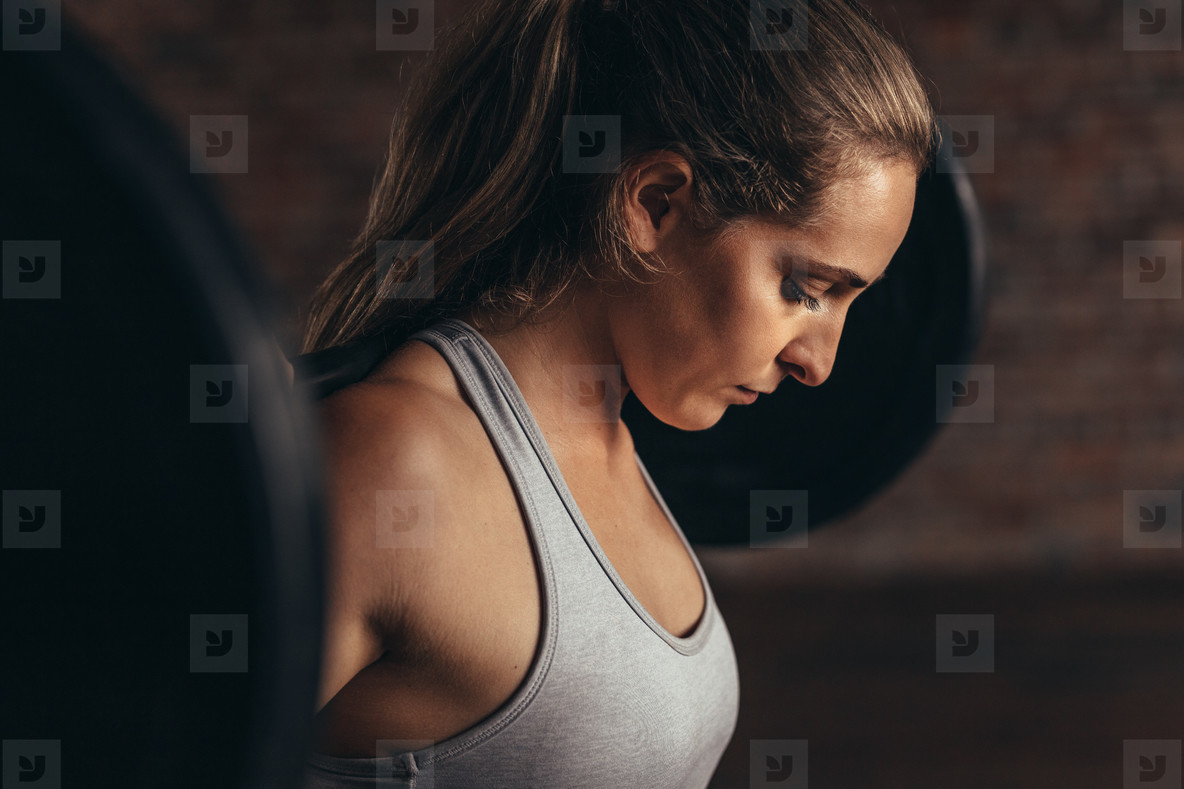 Woman working out at gym with heavy weights