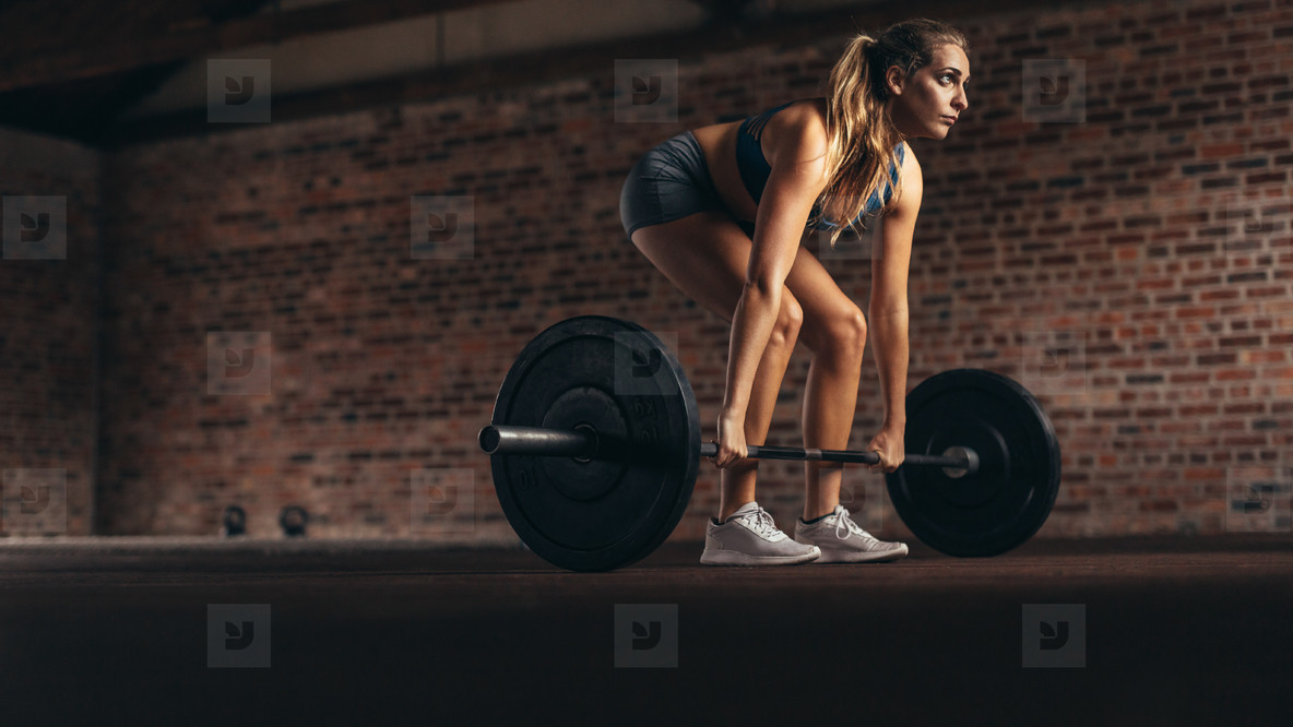 Fitness woman performing weight lifting exercise at gym