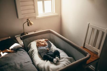 Baby sleeping in a bedside crib