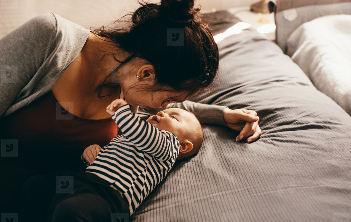 Mother lying on bed with her baby