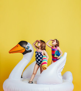Twin girls on inflatable flamingo looking at distance