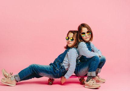 Stylish twin girls sitting together on a skateboard