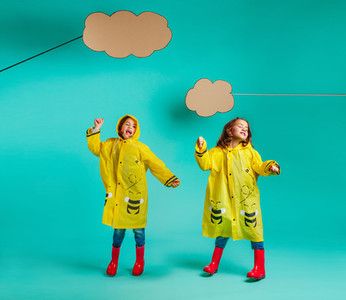 Cute twins girls dancing in raincoats