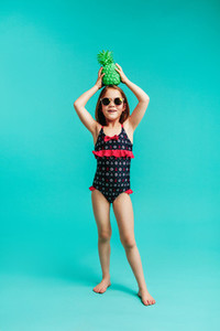 Stylish girl in swimwear with a green coloured pineapple