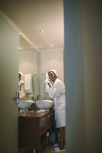 Female in bathrobe wiping her face with towel in bathroom