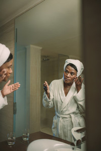 Reflection of mature woman in the mirror applying facial cream