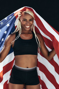 Female athlete celebrating victory holding american flag