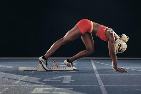 Sprinter using a starting block to start her sprint on a running