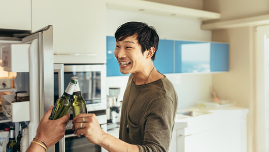 Asian man toasting a bottle of beer with friend